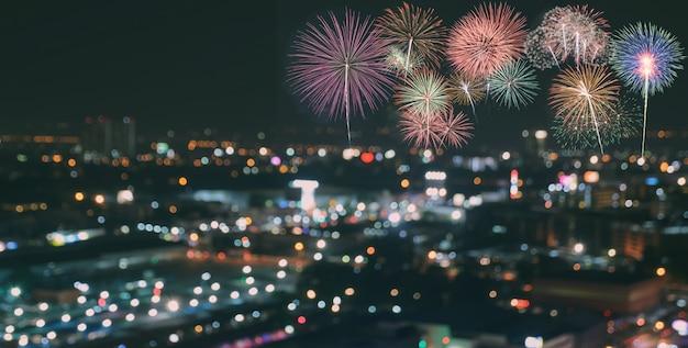 Fuochi d'artificio variopinti sul fondo dell'orizzonte della città della sfuocatura alla notte