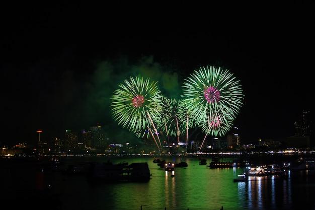 Fuochi d'artificio verde magenta sulla spiaggia e sul colore di riflessione sulla superficie dell'acqua