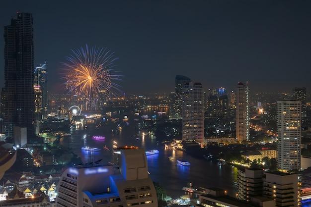 Fuoco d'artificio multicolore che esplode sul lato del fiume di bangkok cityscape per la celebrazione