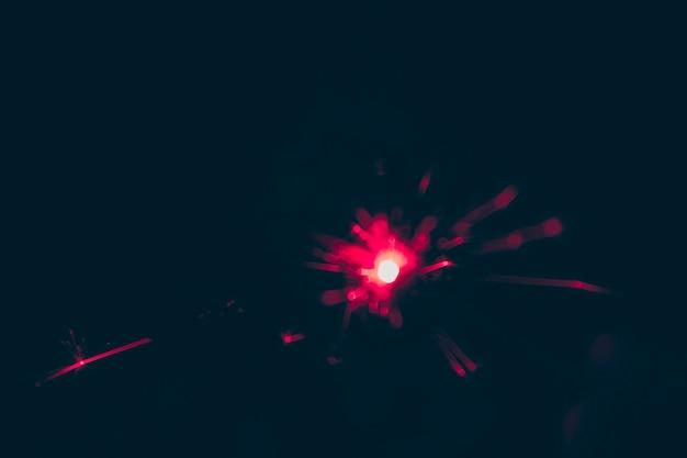 Fuoco d'artificio rosso vago alla vigilia del nuovo anno su fondo nero
