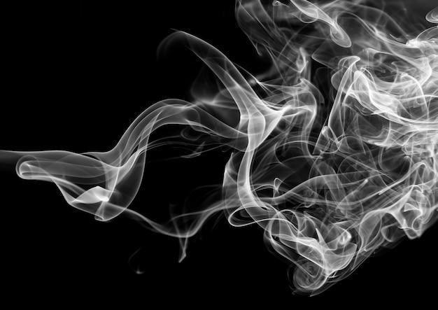 Fuoco dell'estratto bianco del fumo su fondo nero, concetto di oscurità