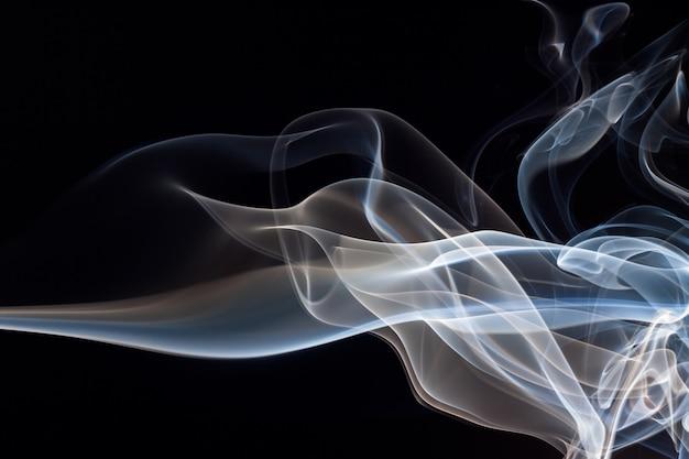 Fuoco dell'estratto blu e bianco del fumo su fondo nero, concetto di oscurità