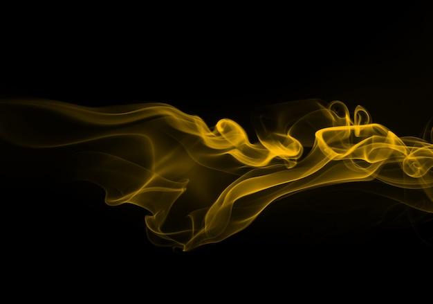 Fuoco dell'estratto giallo del fumo su priorità bassa nera per il disegno. concetto di oscurità