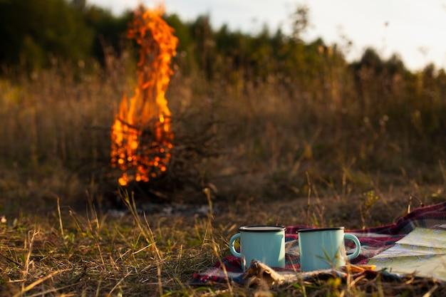 Fuoco fiamma basso angolo con tazze accanto