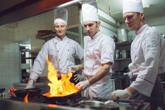 Fuoco in cucina. l'ustione del gas del fuoco sta cuocendo sulla padella di ferro, mescolare il fuoco molto caldo