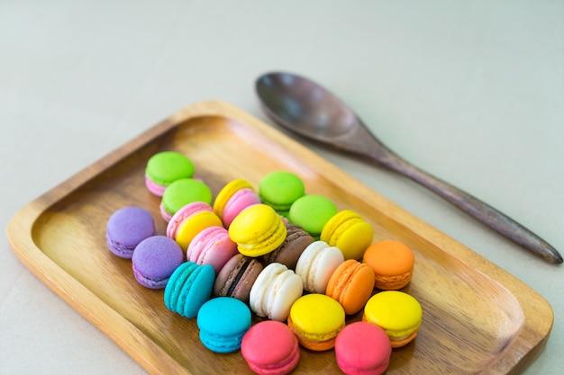 Fuoco molle di macarons pastelli variopinti in piatto di legno sulla tavola con il fondo verde della parete