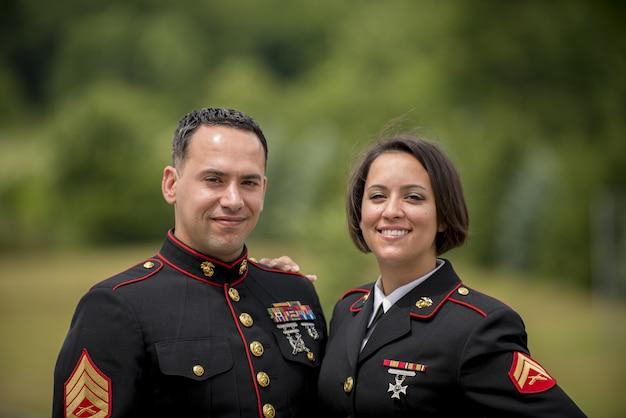 Fuoco poco profondo sparato di un sorridere militare delle coppie
