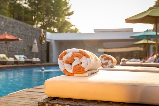 Fuoco selettivo al portasciugamani sul letto della spiaggia intorno alla piscina in hotel.