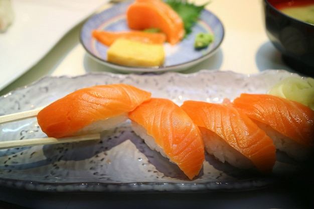 Fuoco selettivo dei sushi di nigiri di color salmone con le bacchette. famoso cibo giapponese concetto di cibo