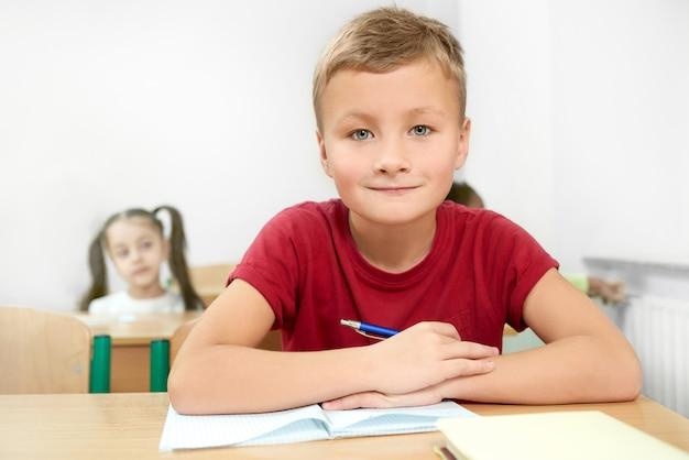 Fuoco selettivo del ragazzo allegro che si siede allo scrittorio in aula