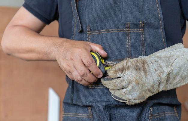 Fuoco selettivo dell'uomo del carpentiere con nastro adesivo di misurazione a disposizione, concetto dell'artigiano.
