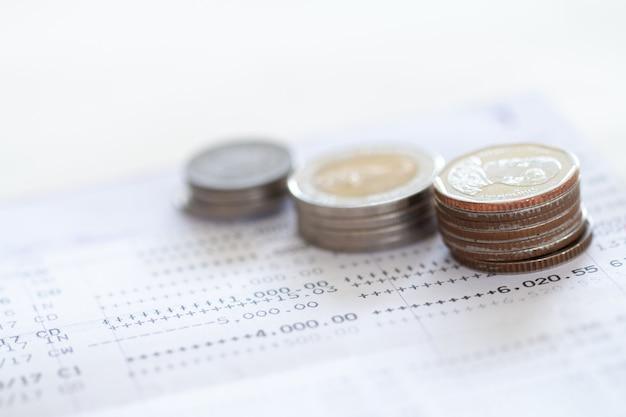 Fuoco selettivo delle monete tailandesi impilate sopra la pagina dell'estratto conto bancario su fondo bianco.