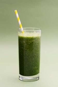 Fuoco selettivo di vetro mescolato del frullato verde, fondo verde. cibo salutare.