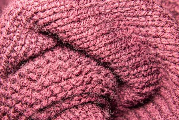 Fuoco selettivo e vista alta vicina di struttura tricottata rossa della lana.