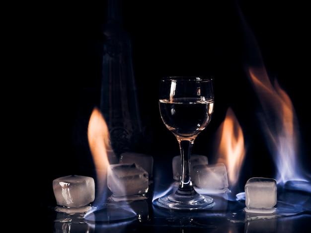 Fuoco sul bicchiere da vino, fuoco sul bicchiere da cocktail, vodka ghiaccio e fuoco