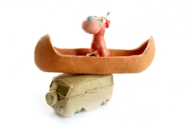 Furgone di vw di plastilina fatto a mano con canoa indiana e cane sopra