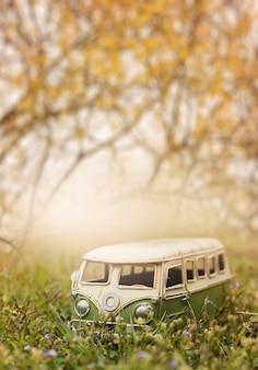 Furgone miniatura d'annata in natura concetto di festa e di viaggio, composizione bassa in profondità di campo.