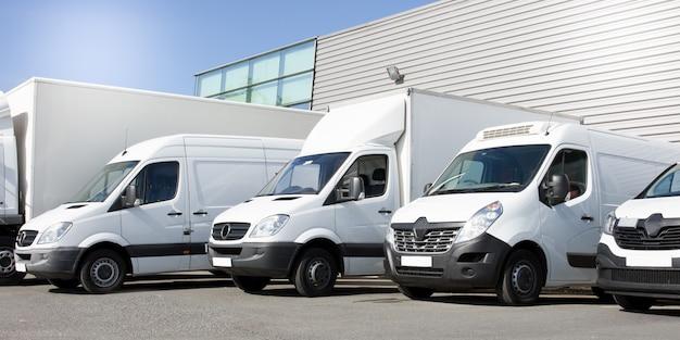 Furgoni bianchi di consegna in camion e auto di servizio davanti all'ingresso di una società logistica di distribuzione di magazzino