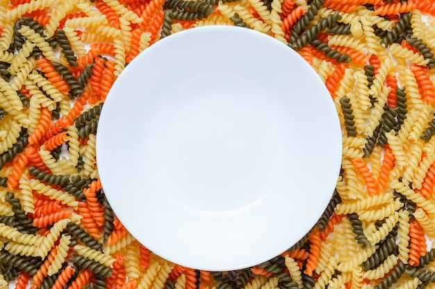 Fusilli colorati con piatto bianco piatto distesi