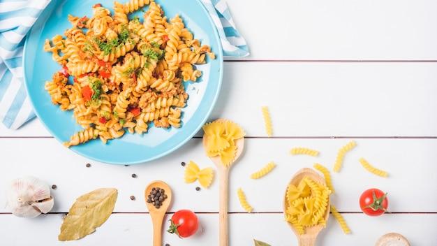Fusilli di pasta di verdure cucinato con ingredienti sul contesto di legno bianco