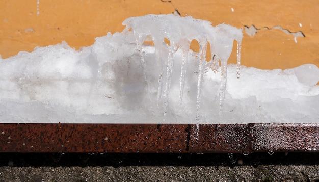 Fusione della neve e ghiacciolo di forme insolite sul bordo arrugginito del metallo contro il vecchio fondo della parete