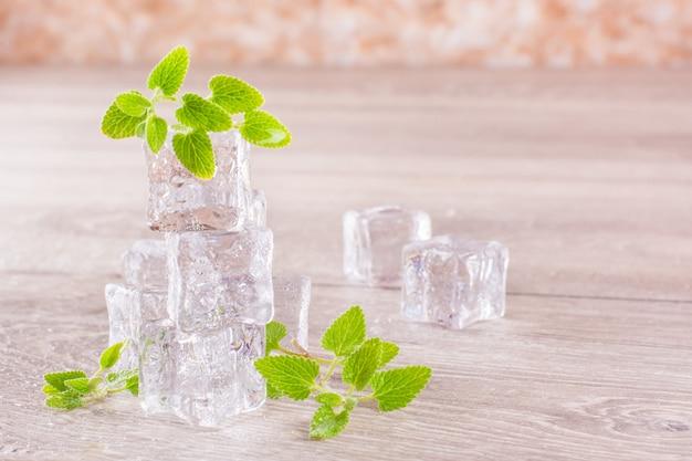 Fusione di cubetti di ghiaccio e foglie di menta in goccioline d'acqua