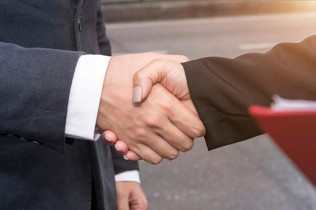 Fusione ed acquisizione. stretta di mano dell'uomo d'affari del responsabile con l'associazione della donna.