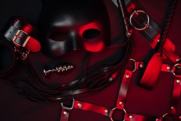 Fustigatore in pelle, manette, cintura, girocollo, maschera e plug anale in metallo