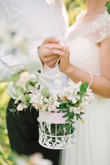 Gabbia per uccelli decorativa bianca con rami di mele in fiore nelle mani degli sposi.