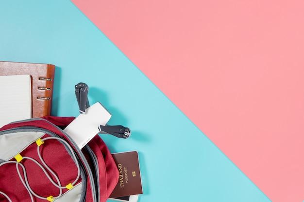 Gadget ed oggetti di viaggio turistico di viaggiatore con zaino e sacco a pelo in zaino con il fuco e gli oggetti su fondo rosa blu