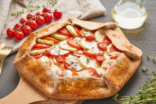Galette fatta in casa con verdure, torta integrale con pomodori, zucchine, formaggio. vista laterale