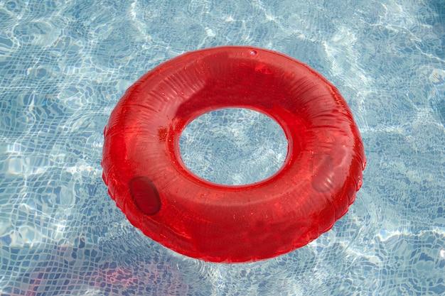 Galleggiante rosso che galleggia nello stagno con acqua blu