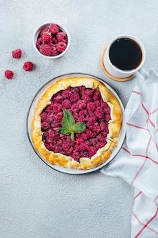 Gallete aperto della torta del lampone casalingo con la tazza di caffè su un fondo della tavola del calcestruzzo leggero