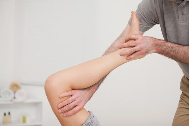 Gamba che viene allungata da un medico in una sala per la fisioterapia