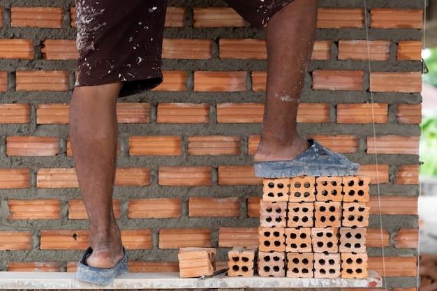 Gamba del primo piano del muratore professionista che pone i mattoni nel nuovo sito industriale
