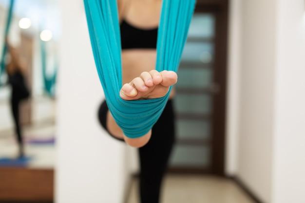 Gamba del primo piano in amaca per esercizi di yoga volare. la donna che fa l'yoga della mosca che allunga si esercita in palestra