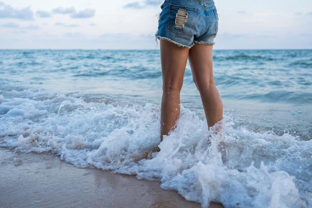 Gamba della donna con l'onda del mare che spruzza sulla spiaggia