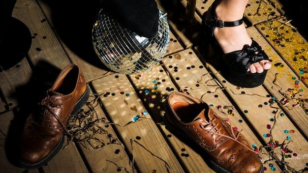Gamba della donna in scarpa vicino a palla da discoteca e stivali