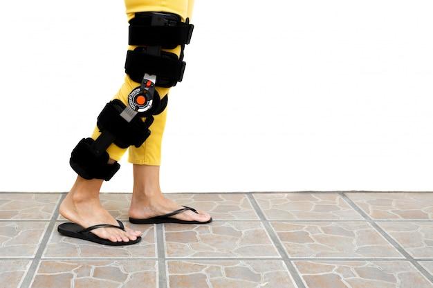 Gamba della donna in un'ortesi che sta sul pavimento isolato.