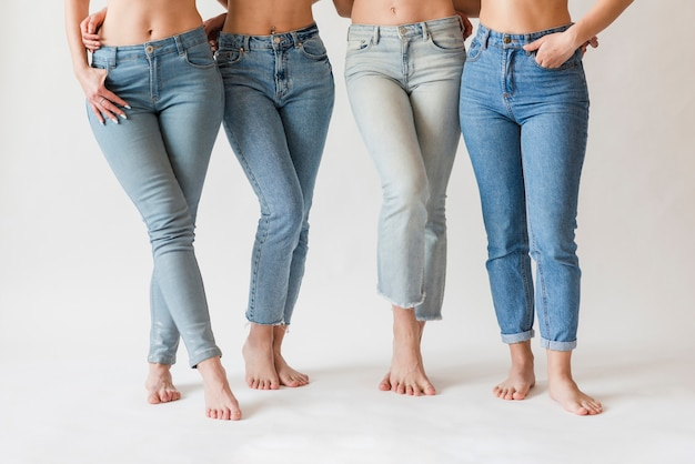 Gambe a piedi nudi del gruppo femminile in jeans