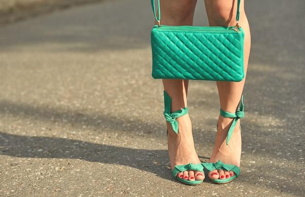 Gambe abbronzate di una ragazza in sandali con tacco retrò e una borsetta in mano
