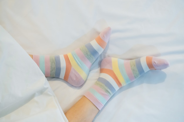 Gambe da donna in colori di calzini alternati, piedistallo sul pavimento in tessuto bianco.