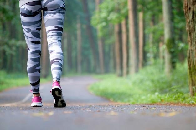 Gambe del corridore femminile di giovane forma fisica pronte per l'esecuzione sulla traccia della foresta