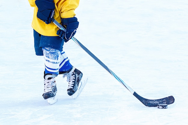 Gambe del giocatore di hockey, bastone e rondella close-up.