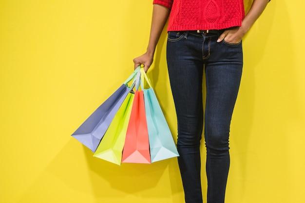 Gambe della donna con i sacchetti della spesa variopinti in una parete variopinta