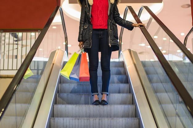 Gambe della donna con i sacchetti della spesa variopinti sulla scala mobile in un centro commerciale