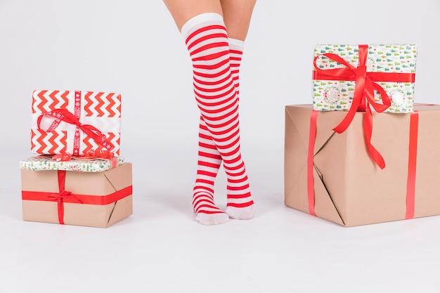 Gambe della donna in calze con scatole presenti