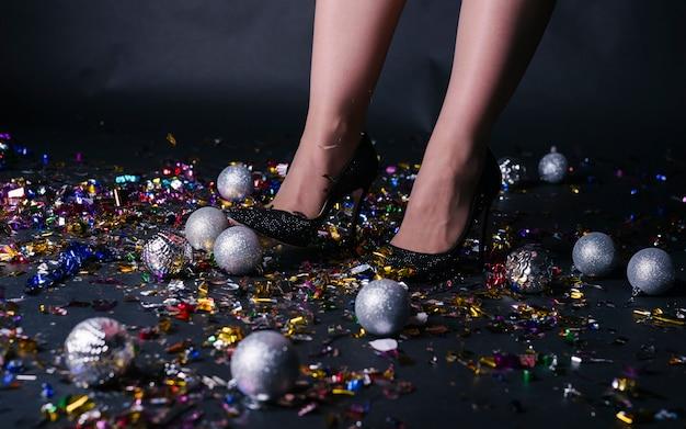 Gambe della donna in piedi sul pavimento festivo