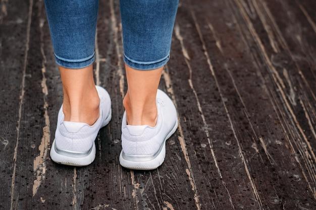 Gambe della donna in scarpe da tennis bianche su un fondo di legno