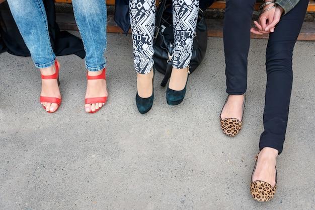 Gambe della donna in scarpe di stile diverso sulla superficie del calcestruzzo